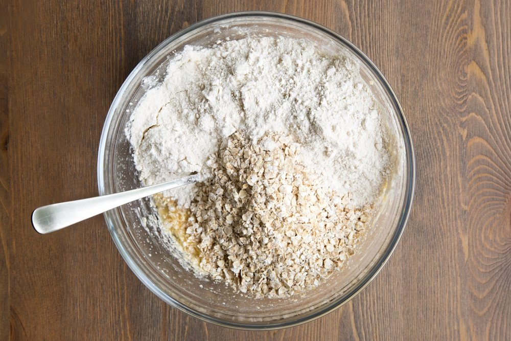 Butter and sugar, milk, egg replacement powder and vanilla creamed together in a bowl, with flour and oats on top.