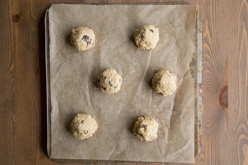 Balls of vegan oat cookie dough on a tray lined with baking paper.