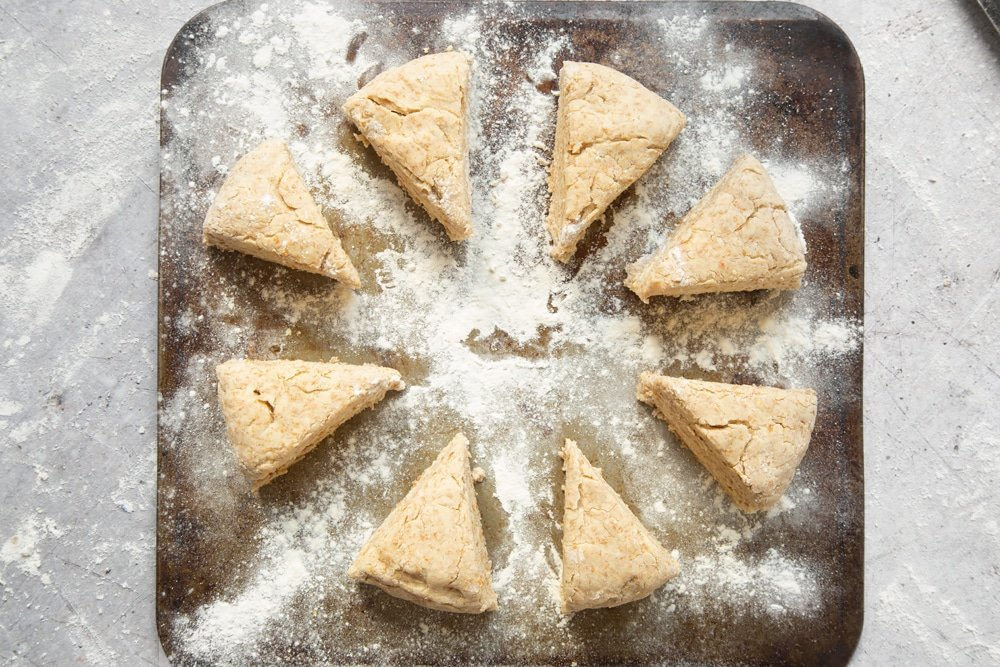 Triangles of scone dough on a floured baking tray