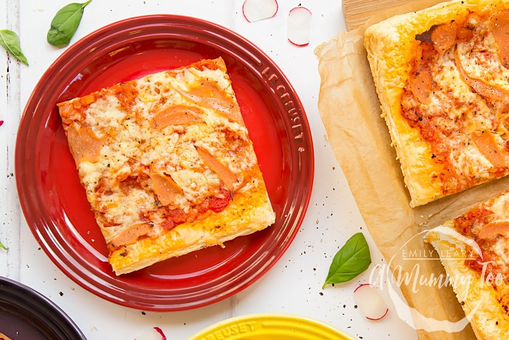 Overhead shot of Pizza style puff pastry slice served on colorful plates with a mummy too logo in the lower-right corner