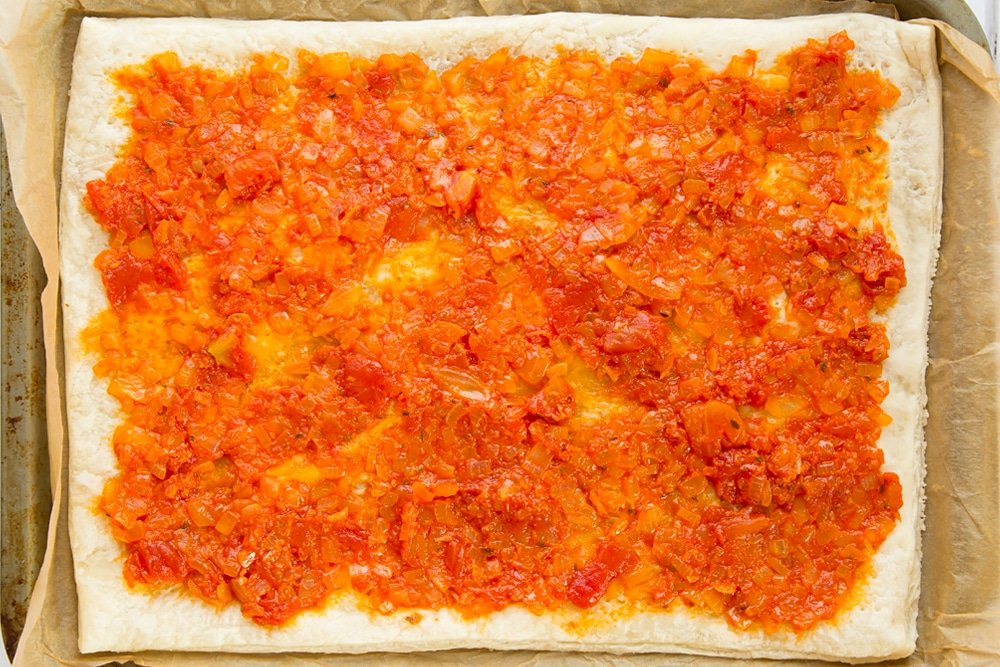 Overhead shot of puff pastry with spread out tomato sauce on a baking tray