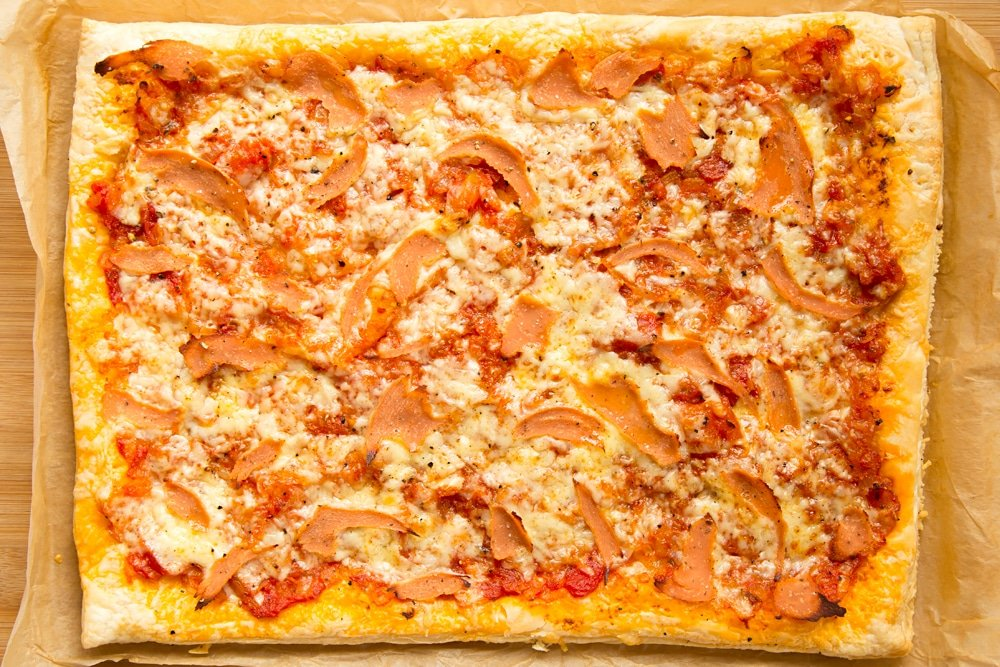 Overhead shot of cooked puff pastry pizza in a baking tray