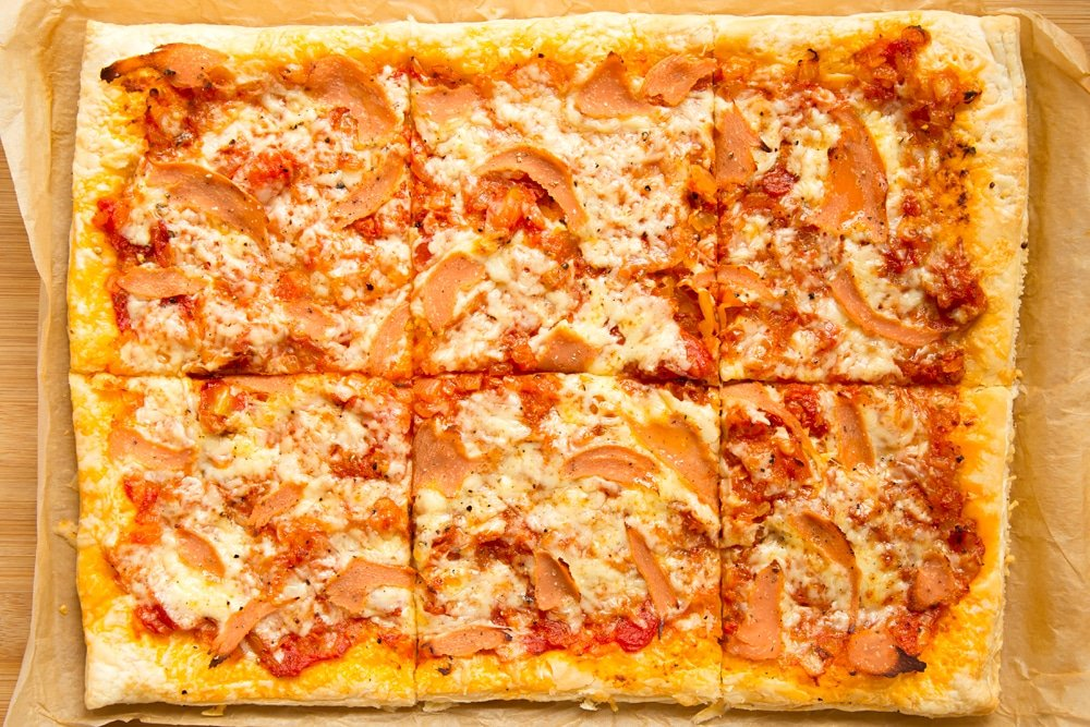 Overhead shot of sliced puff pastry pizza in a baking tray