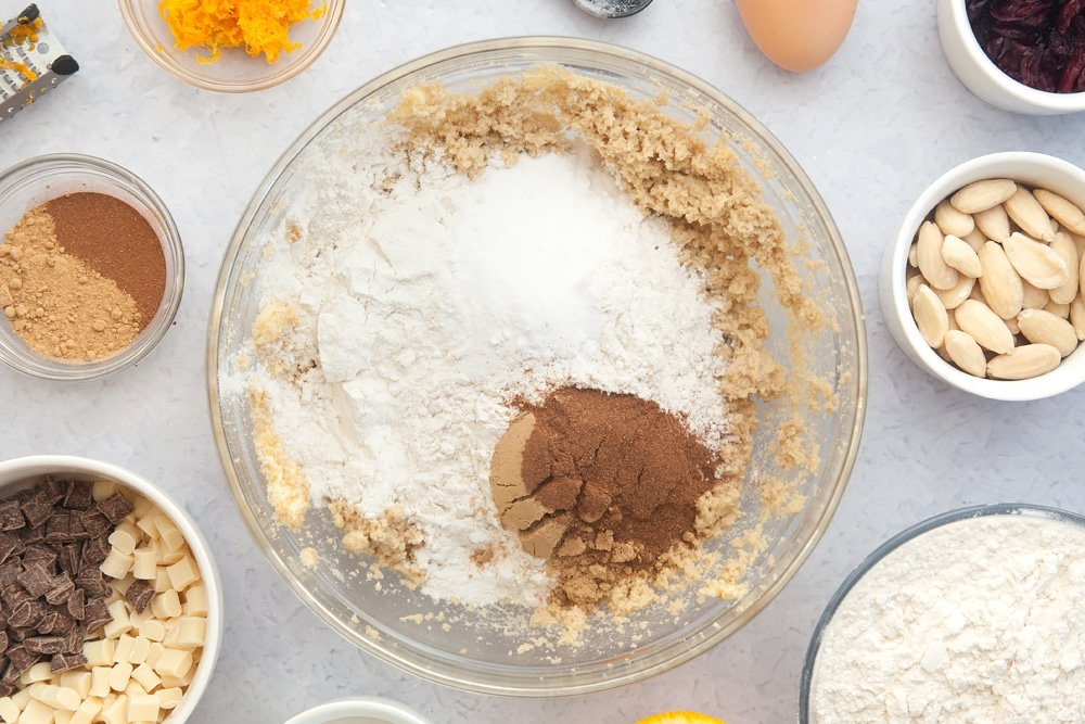 Overhead shot of flour, baking powder, ginger and cinnamon in a large clear bowl