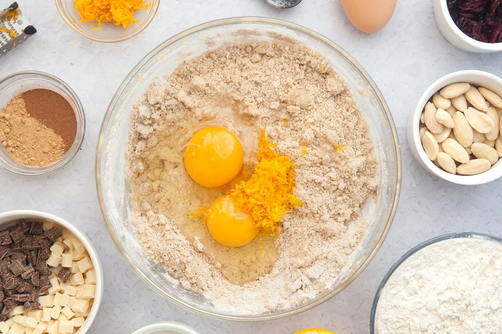 Overhead shot of dough mix, orange zest and eggs in a large clear bowl
