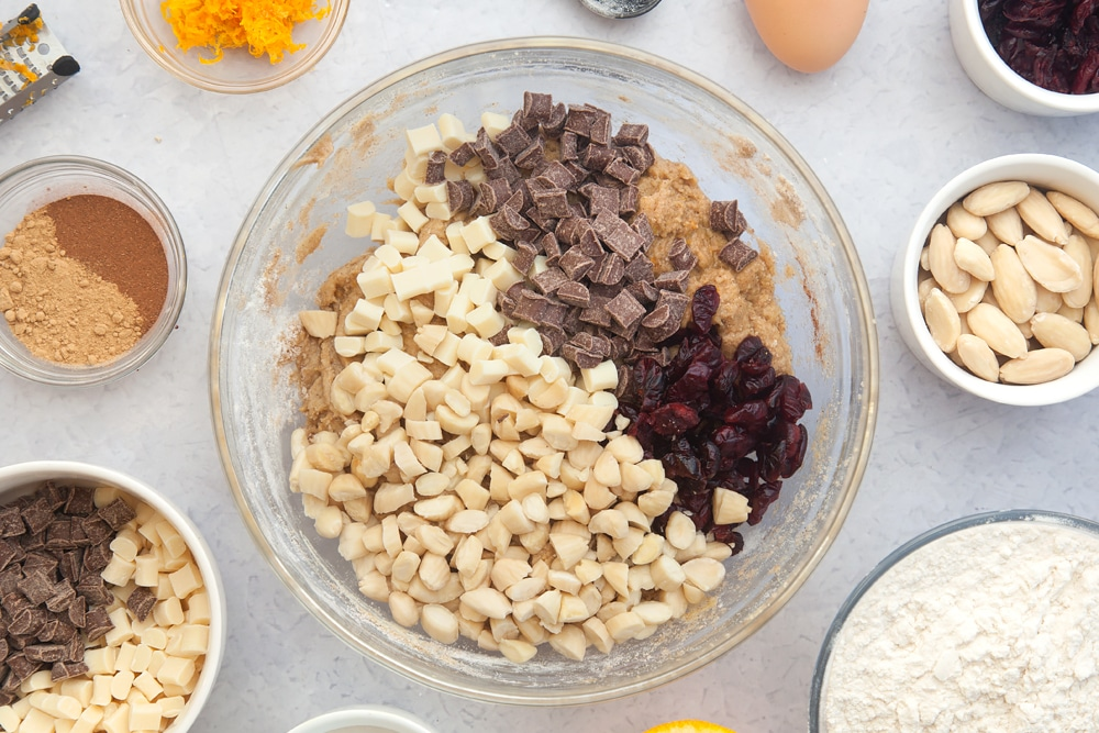 Overhead shot of dough mix, almonds, cranberries and chocolate chips in a large clear bowl