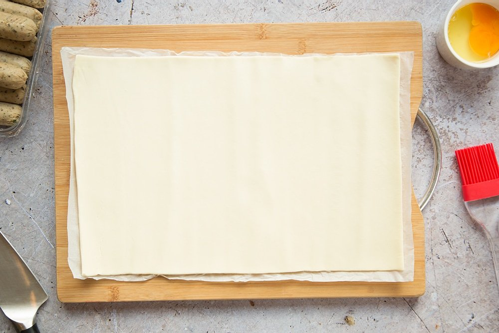 A sheet of puff pastry on a chopping board.
