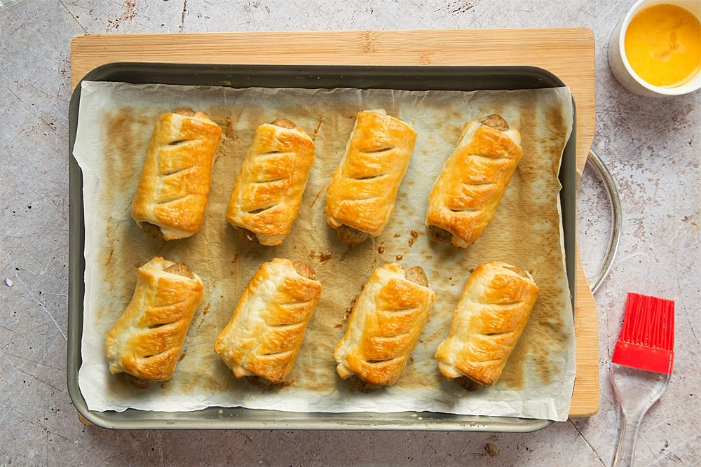 Eight cooked vegetarian sausage rolls on a baking tray lined with baking paper.