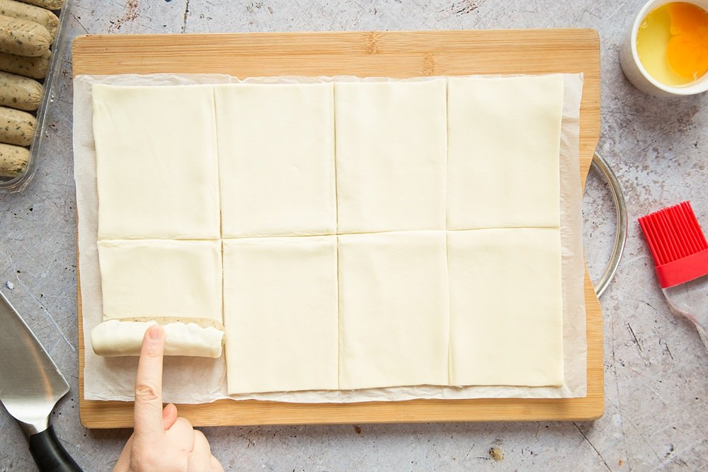 A sheet of puff pastry on a chopping board, cut into eight pieces, with a vegetarian sausage being rolled up in one piece,