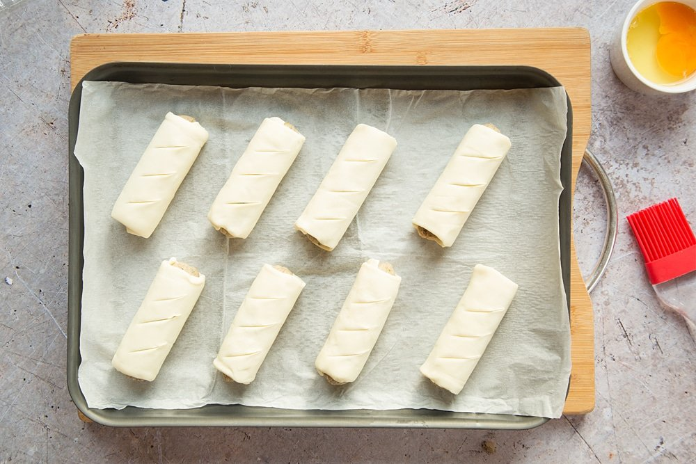 Eight vegetarian sausage rolls on a baking tray lined with baking paper. Three slits cut into the pastry of each one.