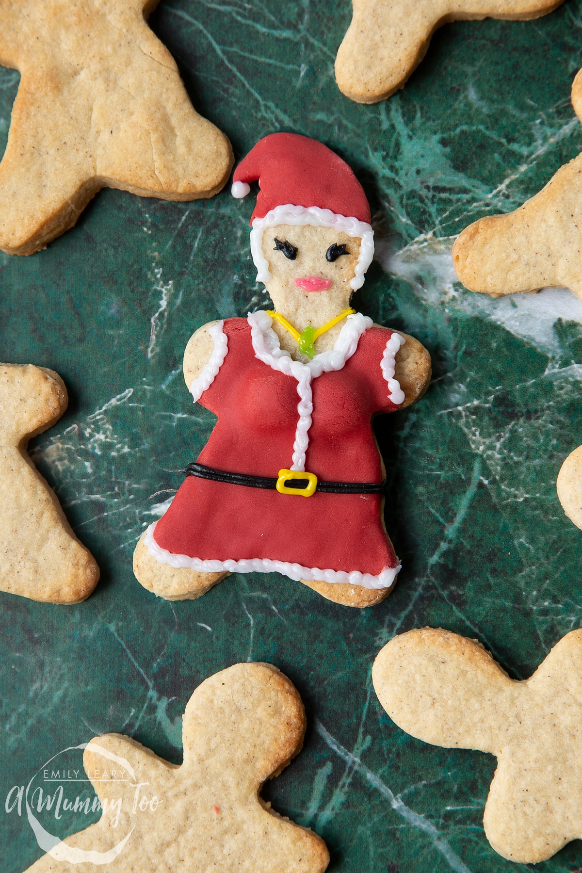 A Mother Christmas cookie, decorated with a suit and hat made from red sugar paste and writing icing.