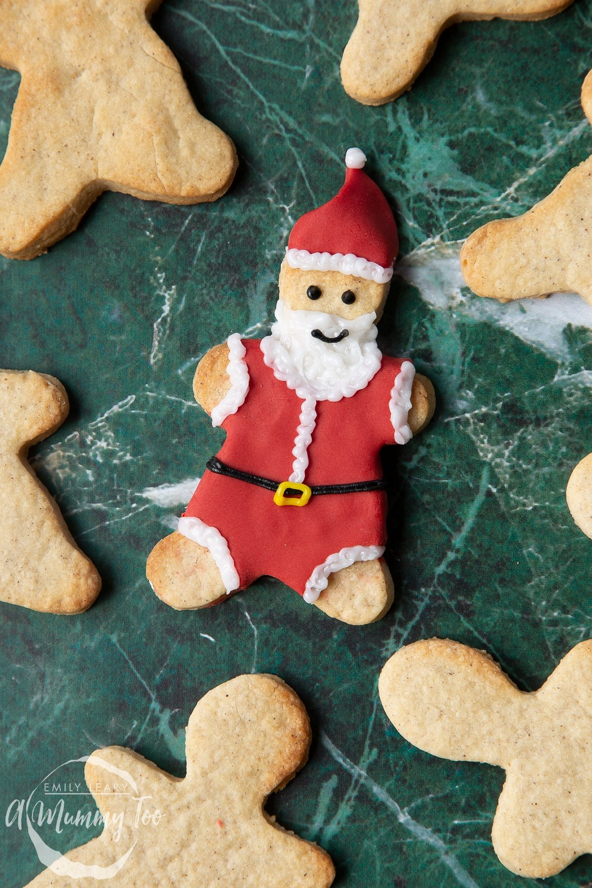 A Father Christmas cookie, decorated with a suit and hat made from red sugar paste and writing icing.