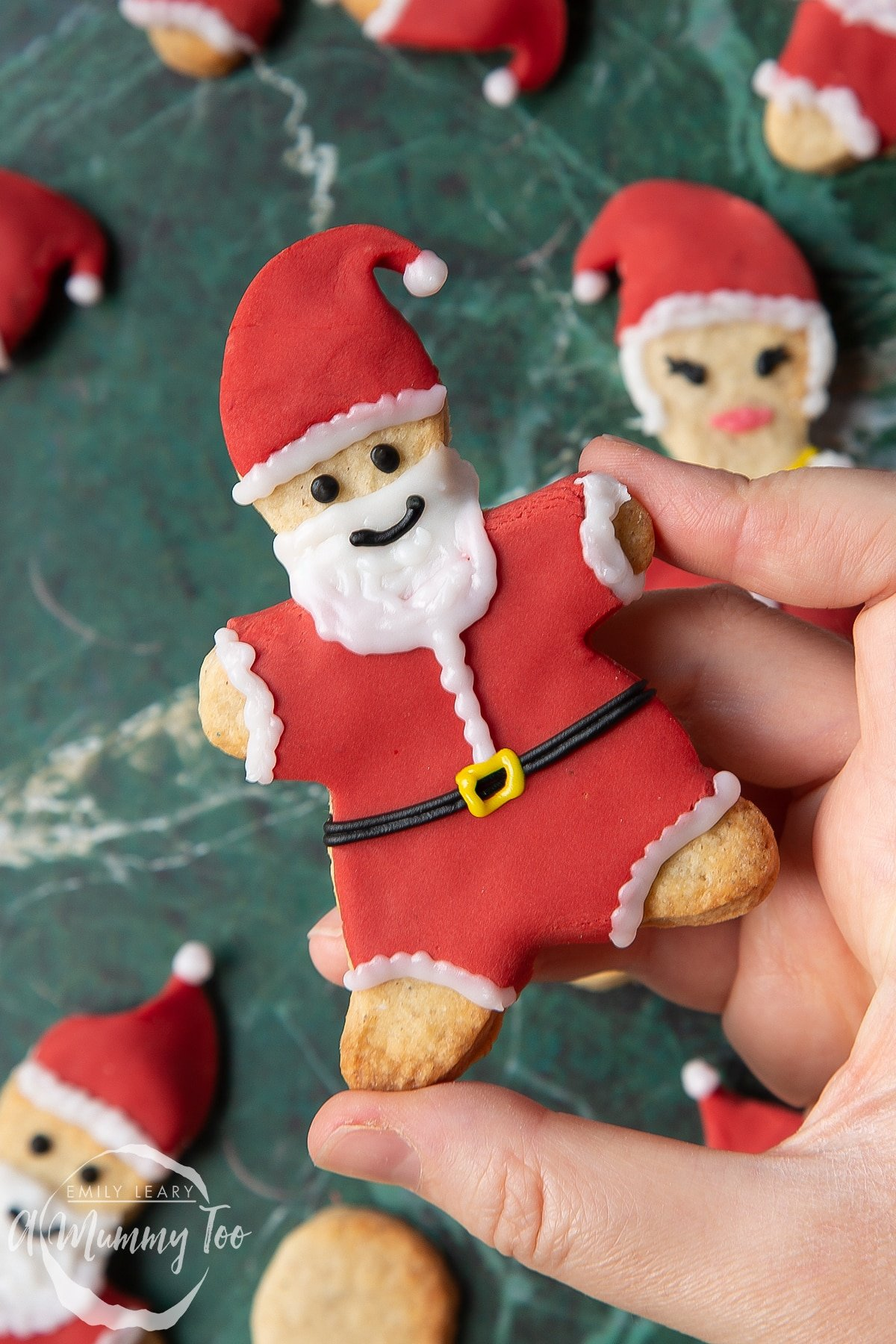 Hand holding a Father Christmas cookie on a green marble surface.