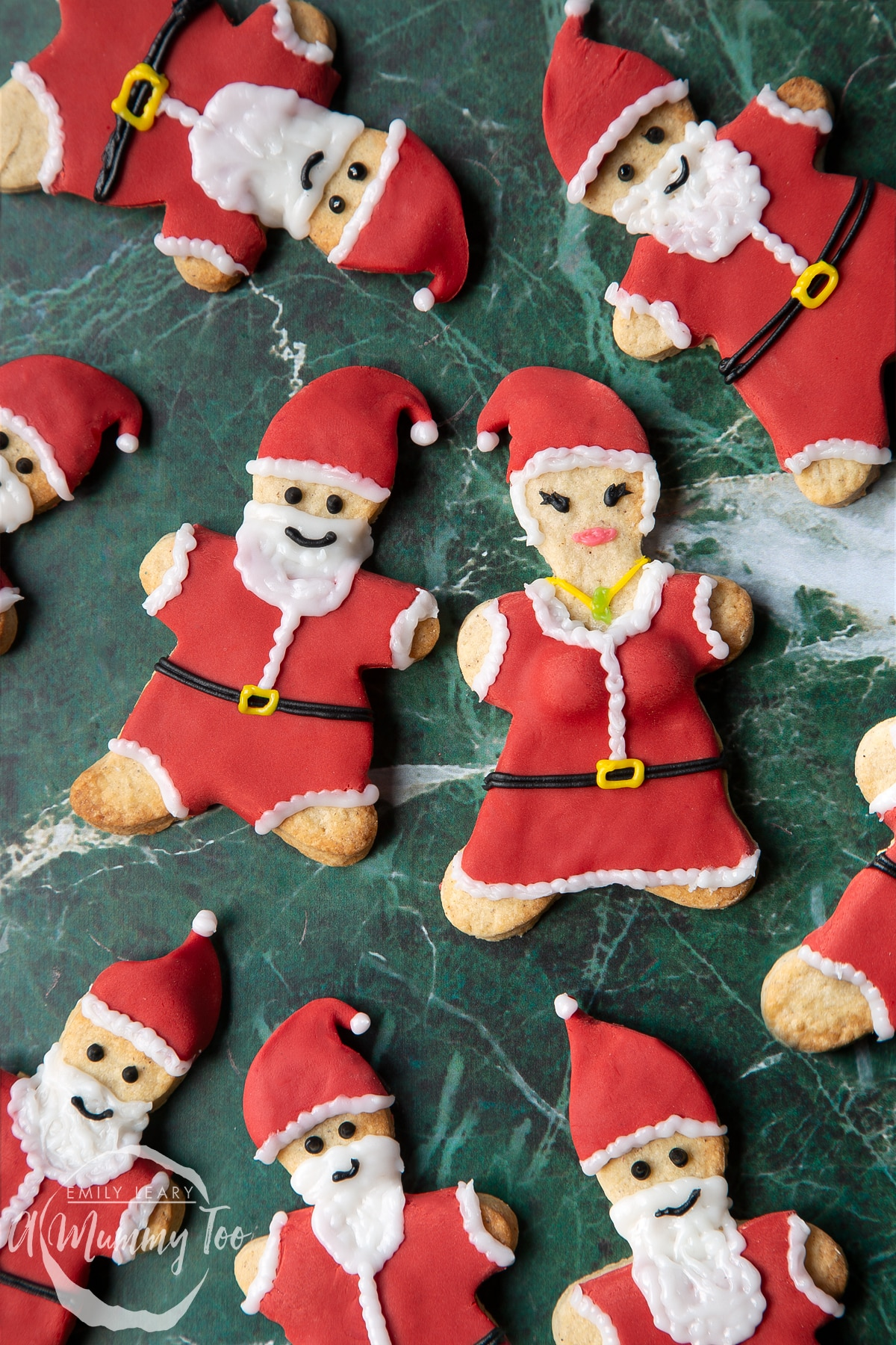 Lots of Father Christmas cookies on a green marble surface. There is also a Mother Christmas cookie.