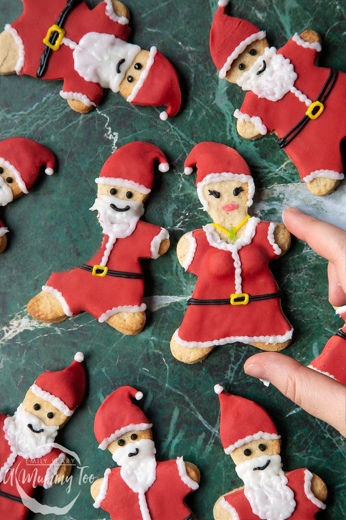 Lots of Father Christmas cookies on a green marble surface. One cookie has a bite take out of it. A hand reaches to take a Mother Christmas cookie.
