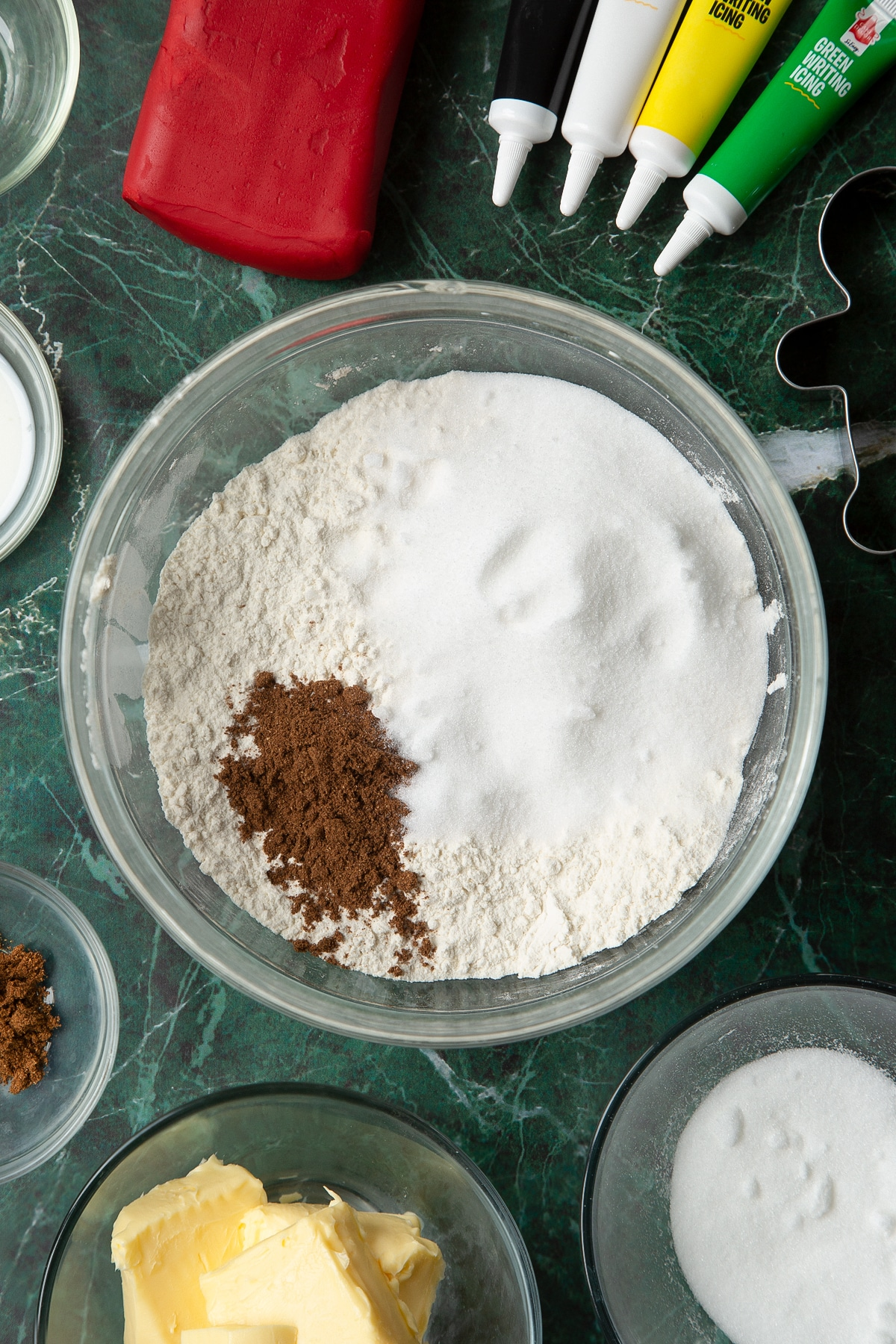 Flour, sugar and mixed spice in a glass mixing bowl, surrounded by ingredients to make Father Christmas cookies.