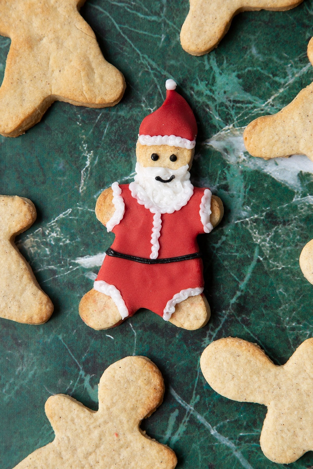 A cookie in the shape of Father Christmas, decorated with a suit and hat made from red sugar paste and writing icing.