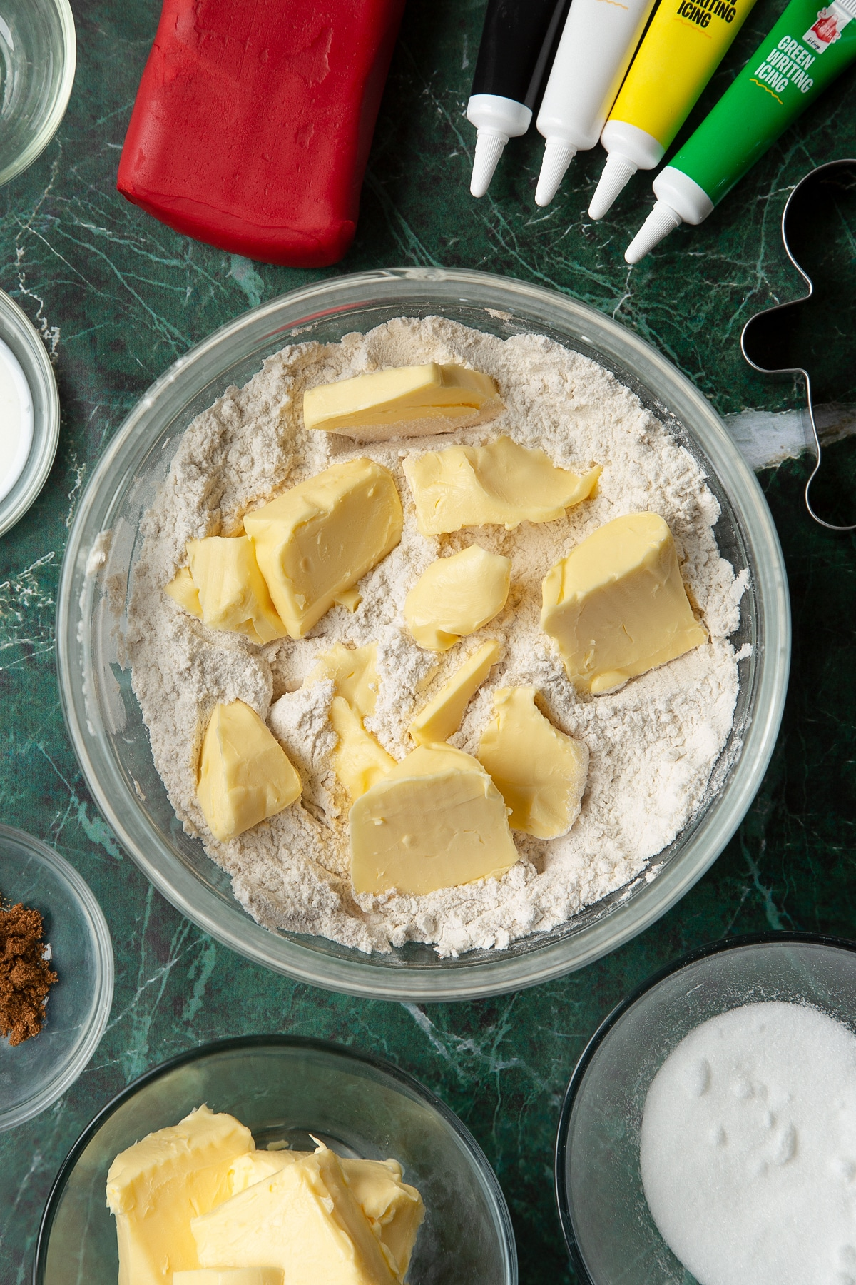 Flour, sugar and mixed spice combined in a glass mixing bowl with butter on top. The bowl is surrounded by ingredients to make Father Christmas cookies.