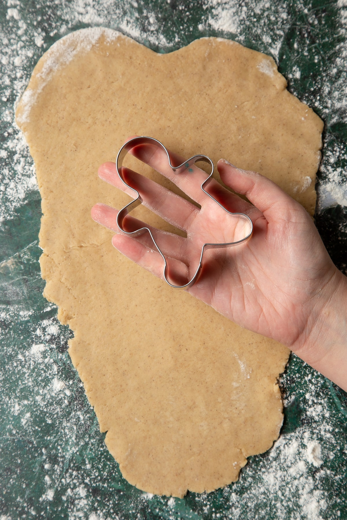 Hand holding a gingerbread man cutter about the size of the palm. Below it, cookie dough is rolled out.