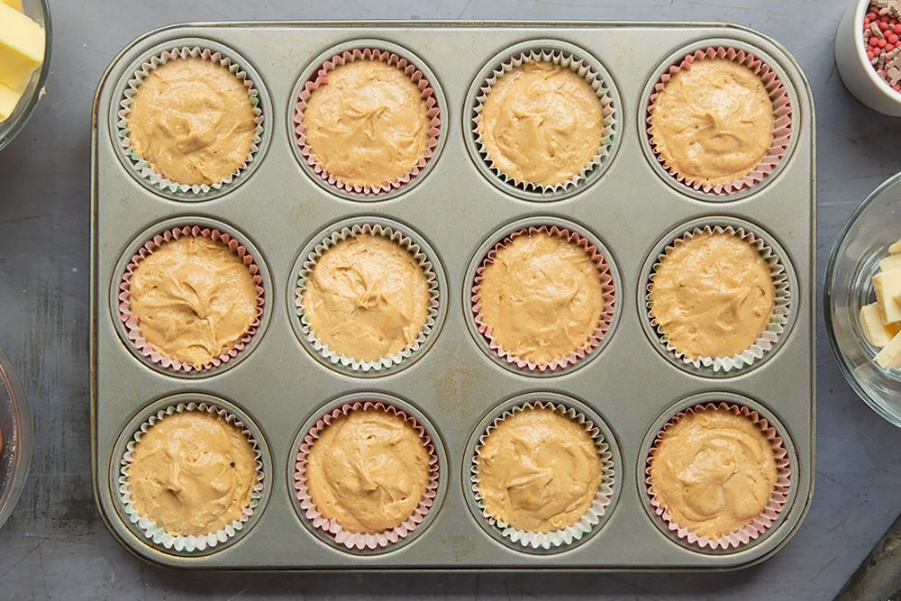 A twelve hole muffin tray lined with muffin cases and the spiced Christmas cupcakes with marzipan frosting cake mixture.