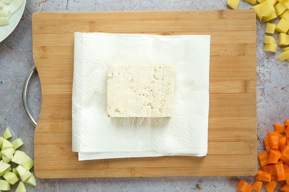 Overhead shot of tofu placed on some kitchen towel on a wooden board