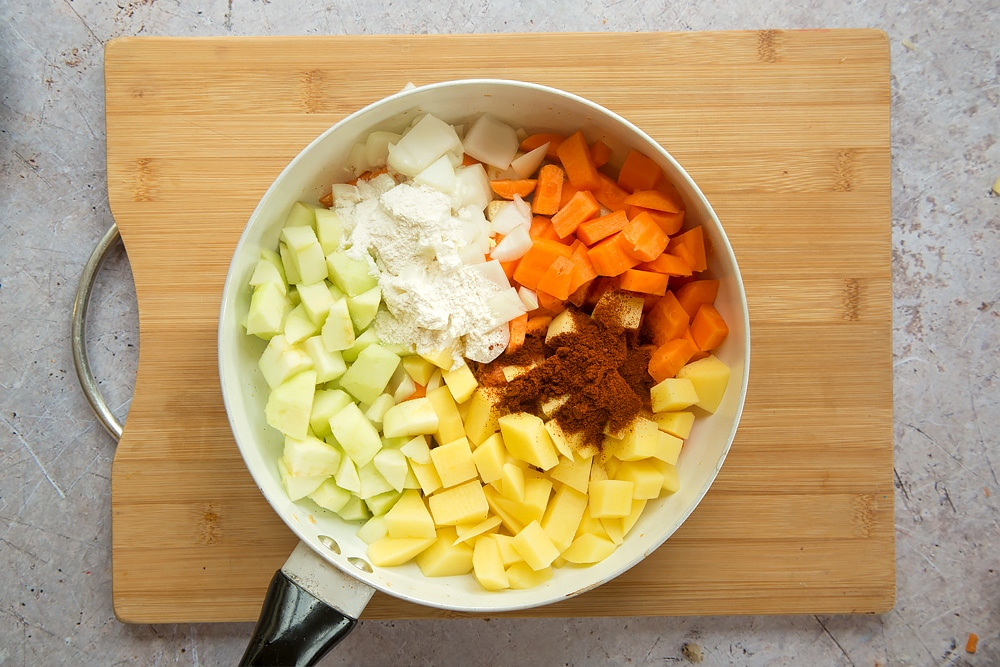 Overhead shot of sultanas, onion, carrots, apple, potato, curry powder and flour in a large white pan