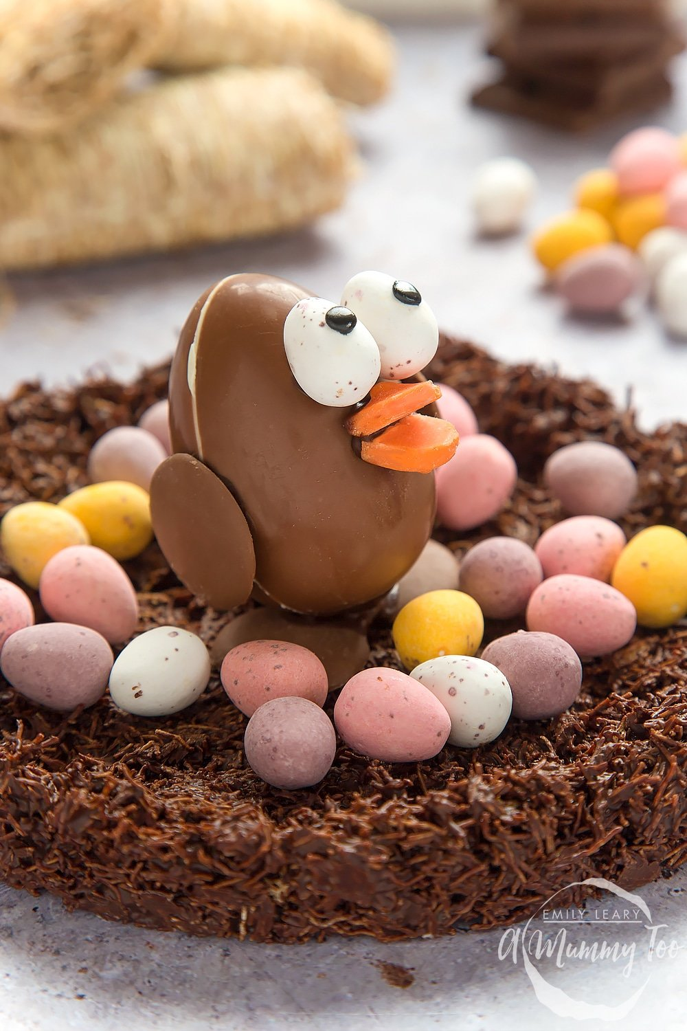 side angle shot Easter chocolate egg chick in a wheaty chocolate nest with a mummy too logo in the lower-right corner