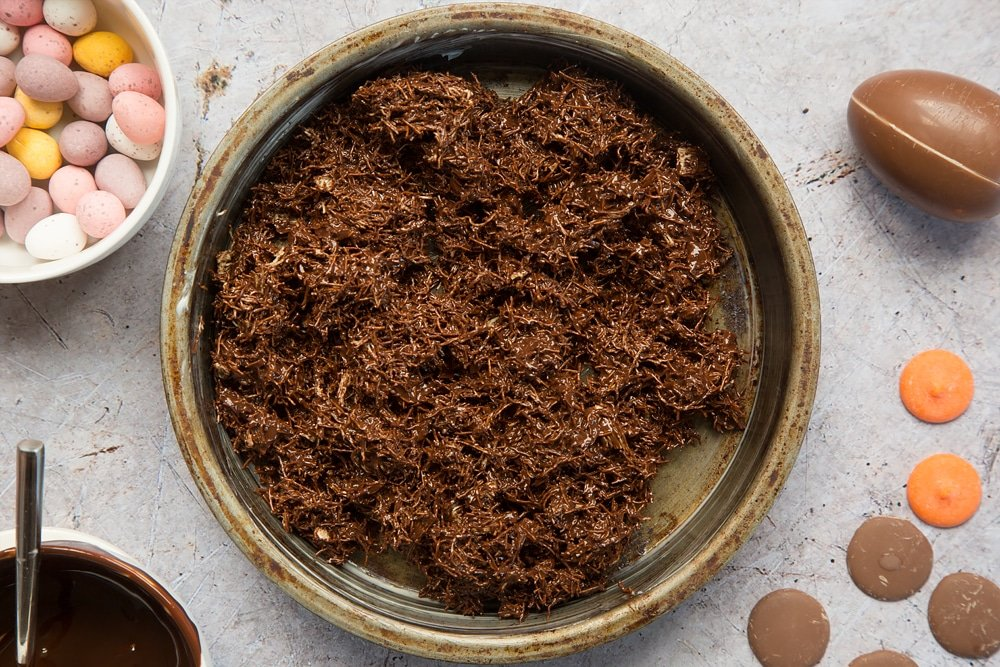 Shredded wheat covered in melted chocolate, shown inside a greased sandwich tin
