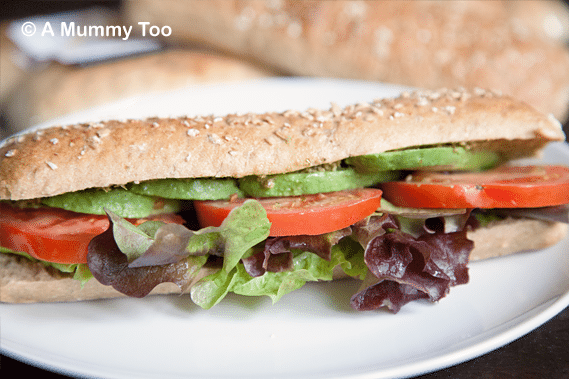 wheat sub sandwich with green pesto, sliced avocado, lettuce and beef tomato slices