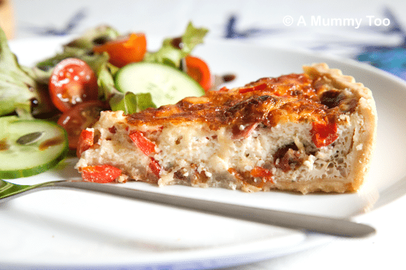 A slice of red pepper quiche with sun dried tomato and salami