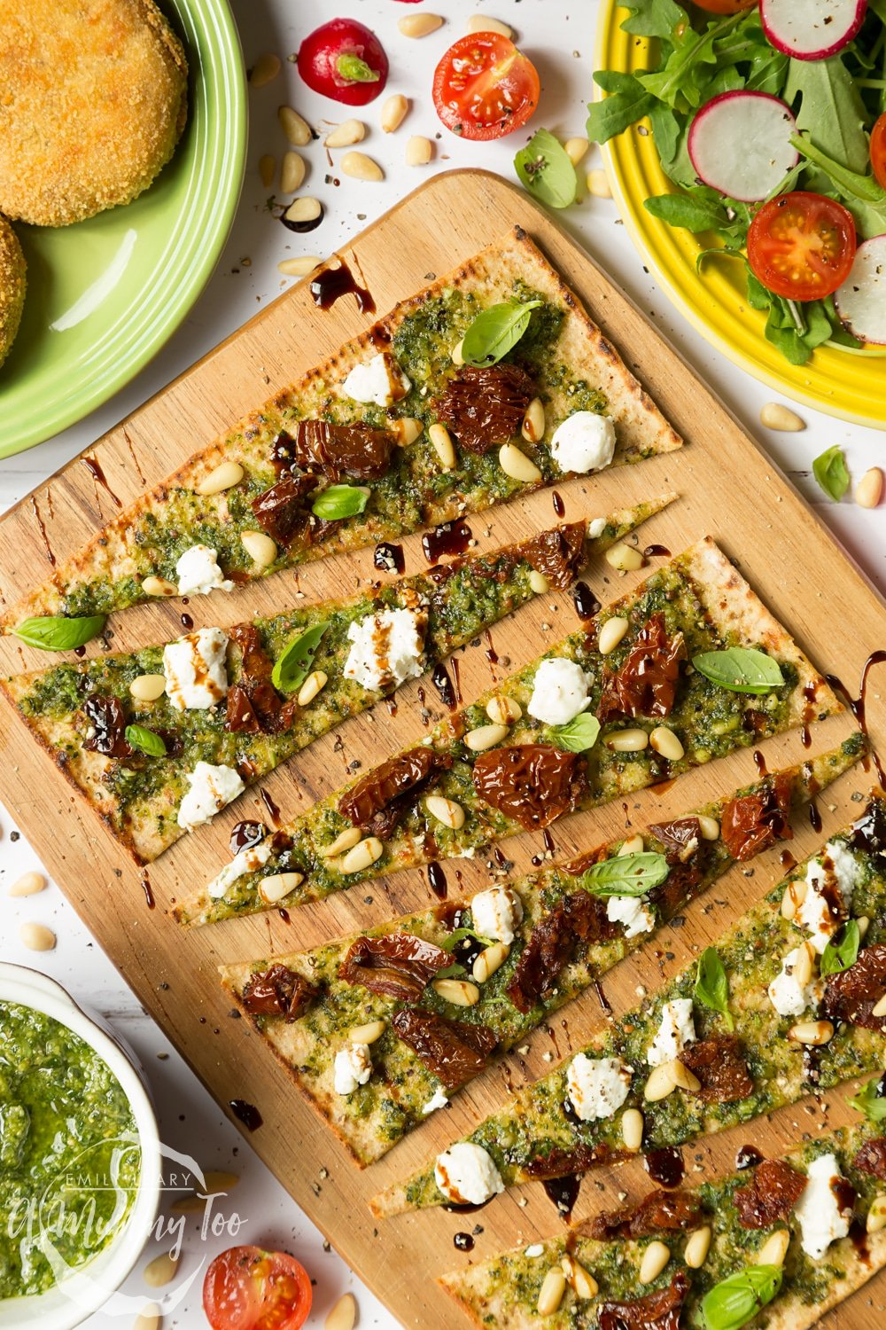 Pesto flatbread pizza topped with goat's cheese, pine nuts and sundried tomatoes