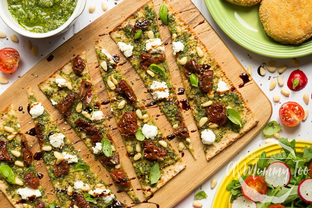 Pesto flatbread pizzas, sliced and served with a side salad