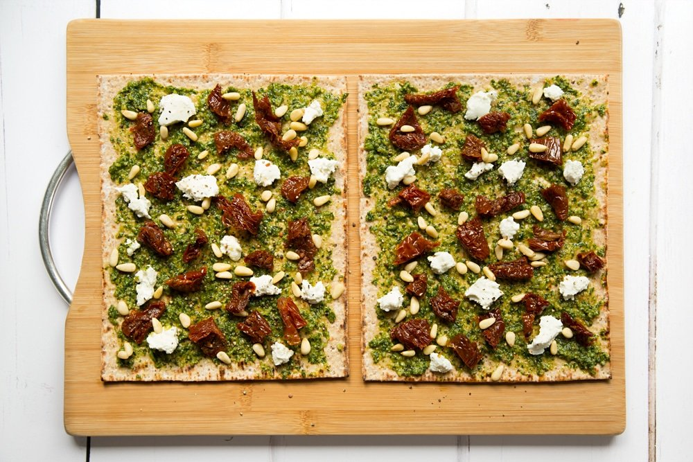 Top the pesto flatbread pizzas with goats cheese, sundried tomatoes and pine nuts