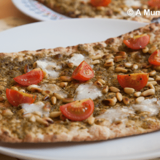 Pesto pizza with toasted pine nuts, goats cheese and cherry tomatoes (recipe)