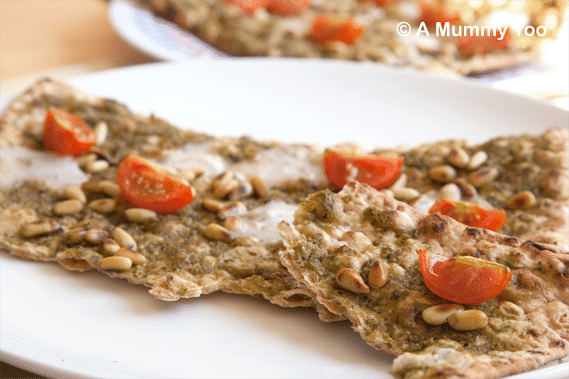 Pesto-pizza-with-toasted-pine-nuts,-goats-cheese-and-cherry-tomatoes