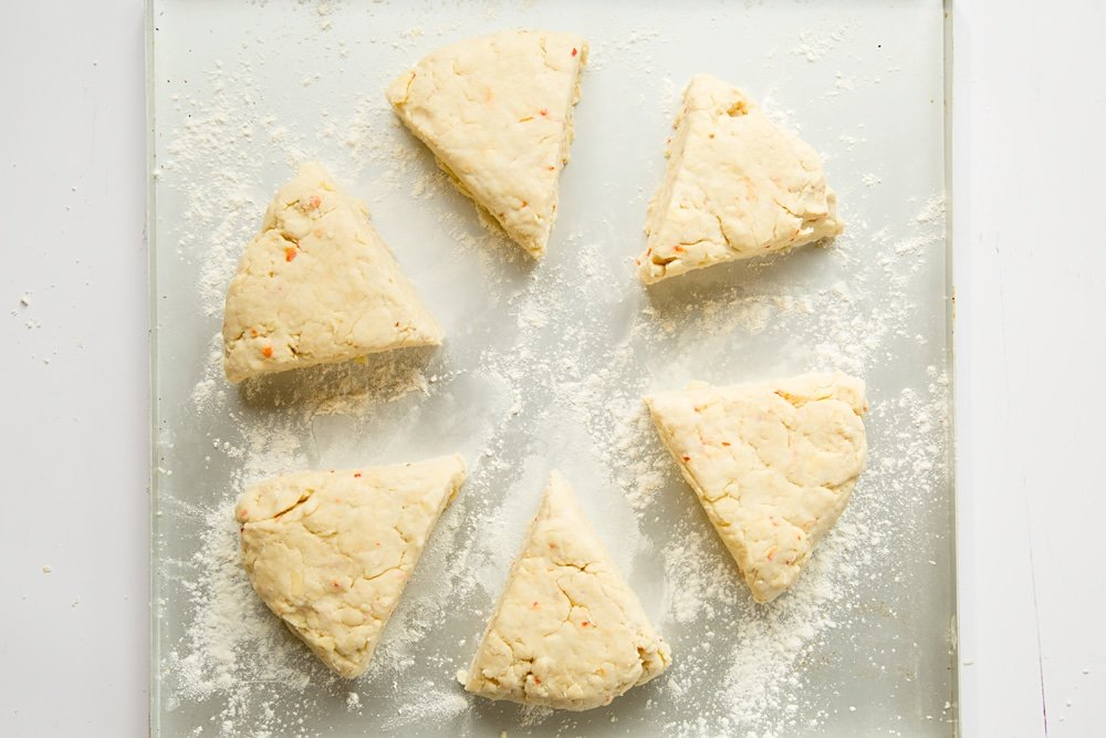 Chilli cheese savoury scone triangles on a floured baking tray