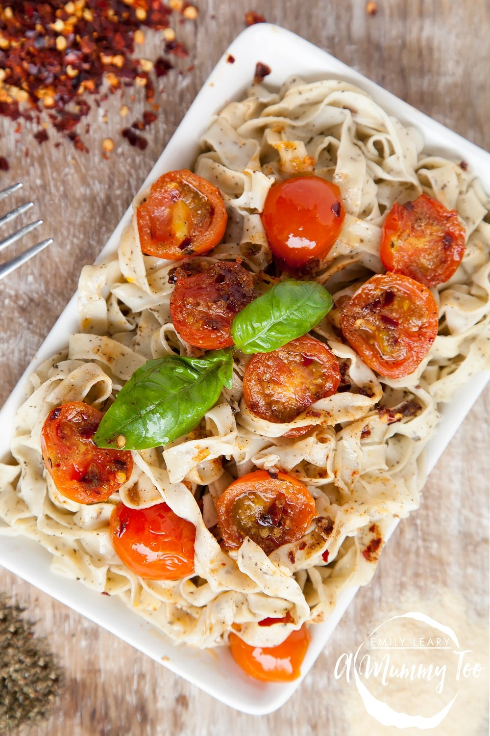 Basil tagliatelle with fiery cherry tomatoes served on a plate