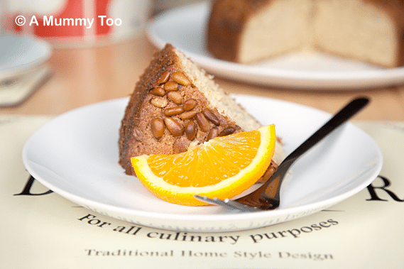 Pine nut crusted orange cake (a Kew's Global Kitchen Cookbook recipe), shown sliced served with a slice of orange