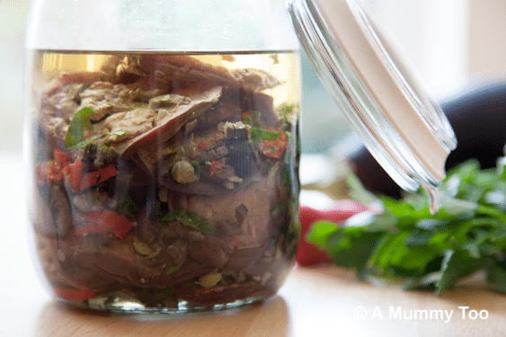 Preserved aubergines with coriander, chilli and capers in a glass jar