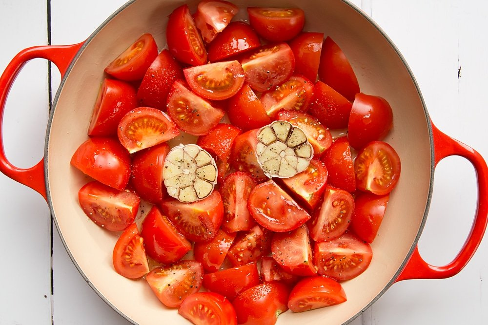 Sliced tomatoes and garlic in a pan