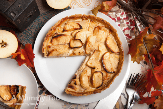 Apple custard tart with cinnamon, shown in an Autumnal place setting