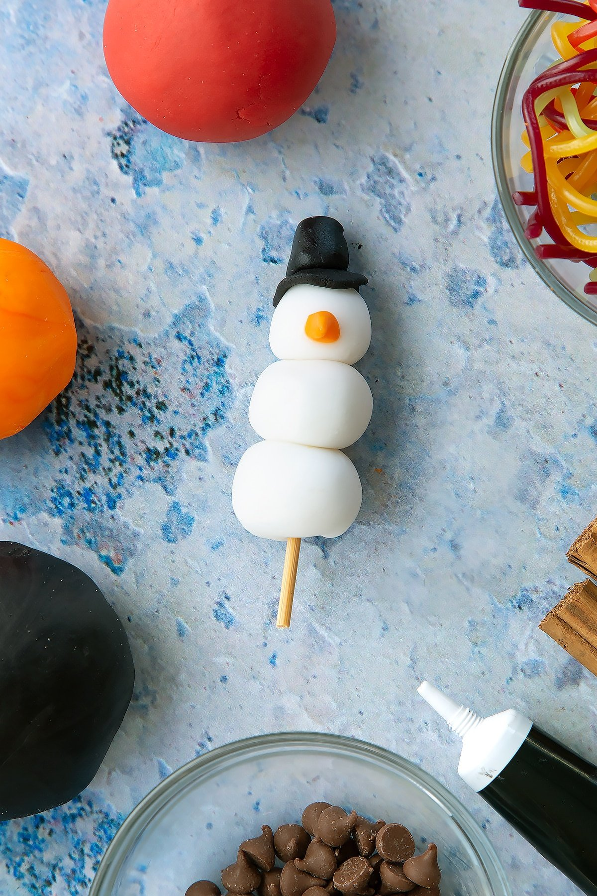 Overhead shot of the snowman made out of sugar paste that will sit on top of the snowman cupcakes.