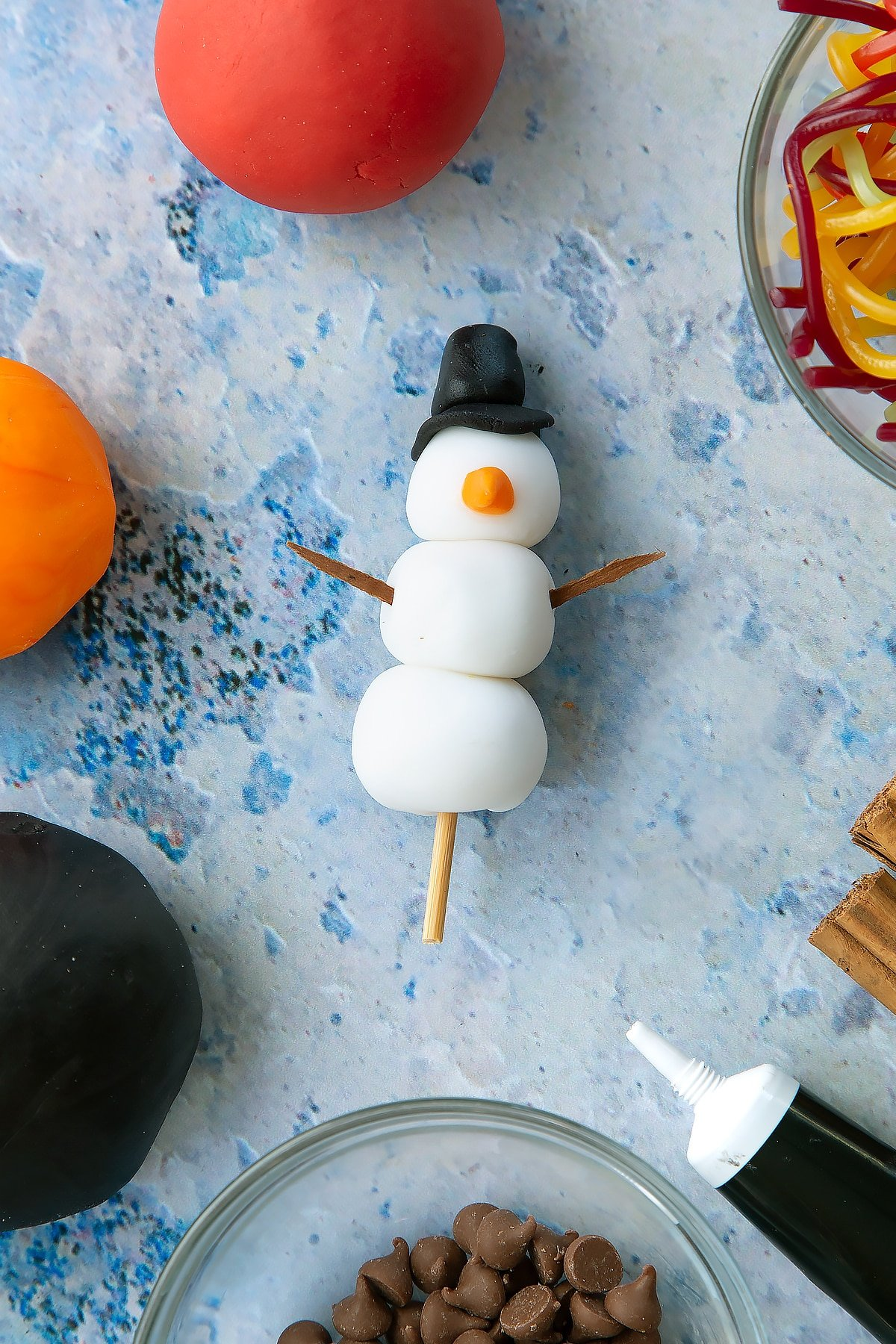 Adding the cinnamon bark to the snowman made of sugar paste. This cinnamon bark is used as arms.