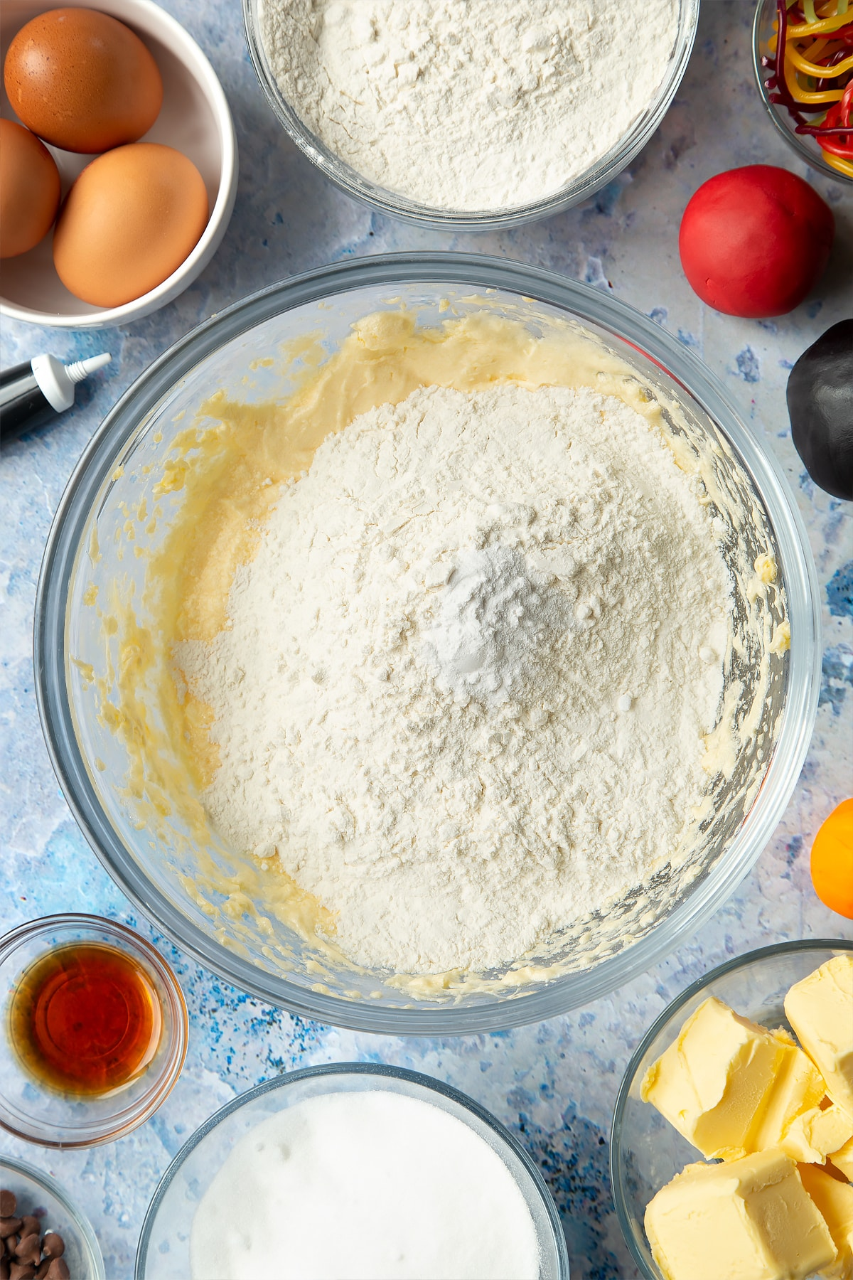 Overhead shot of adding flour and baking powder to the snowman cupcakes mixture.