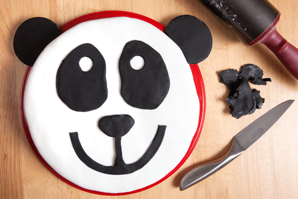 A fun panda cake recipe, made with a vanilla sponge cake topped with white icing and black icing decorations