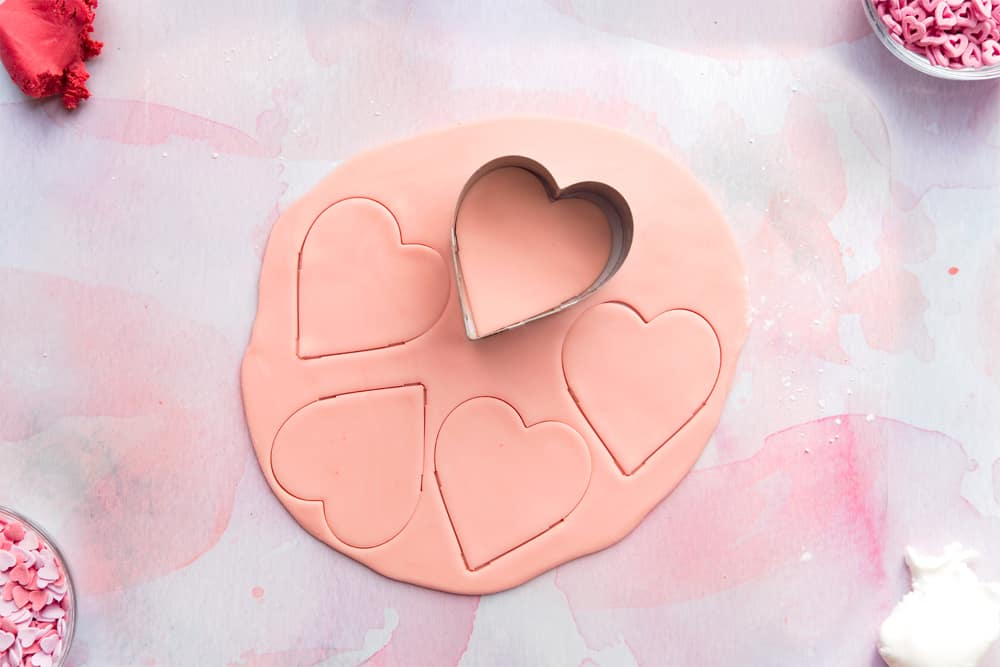 Overhead shot of a heart shaped cookie cutter cutting out pink heart shaped fondant