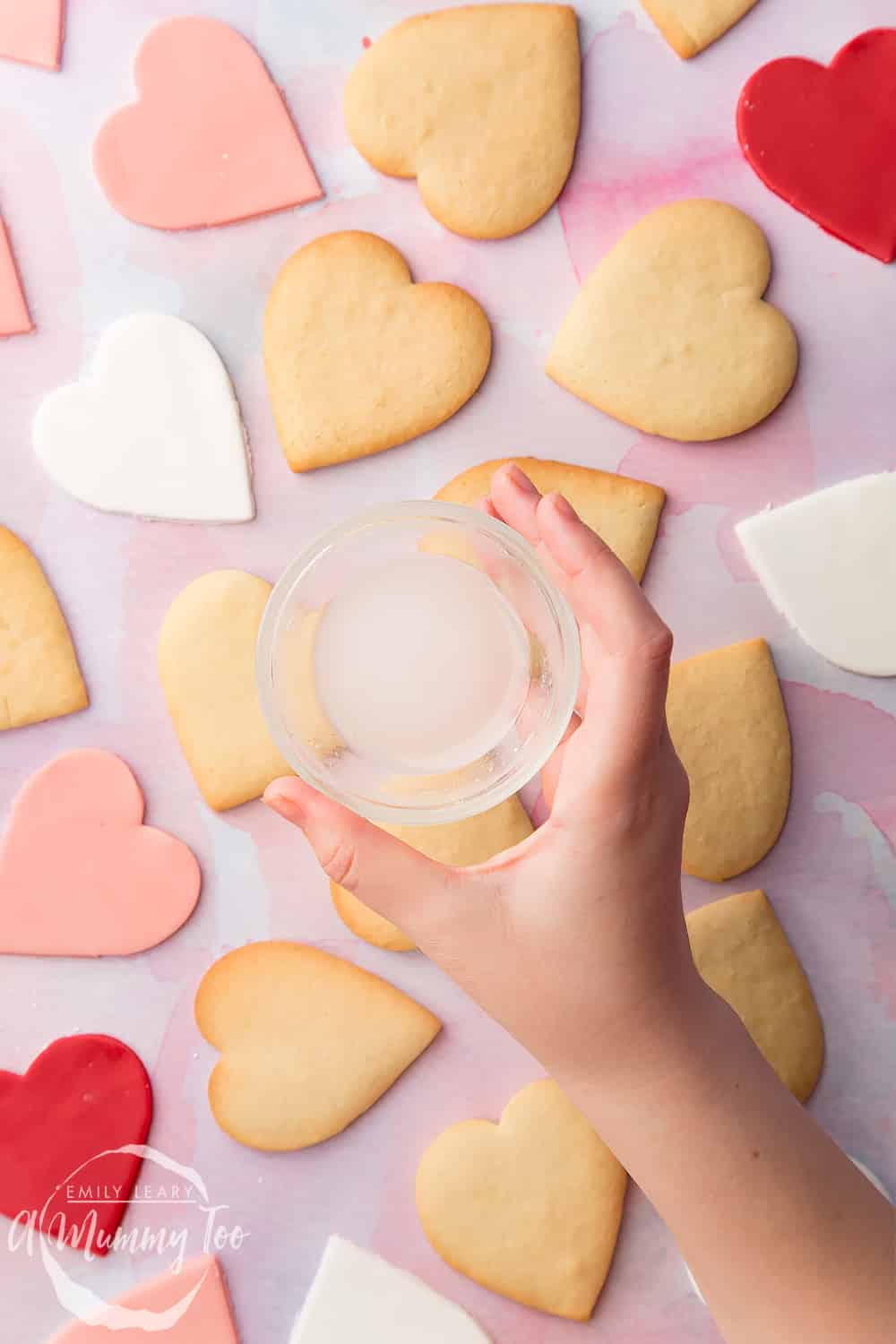 Overhead shot of a hand holding a small clear dish with icing sugar over Heart biscuit for Valentine's Day with a mummy too logo in the lower-right corner