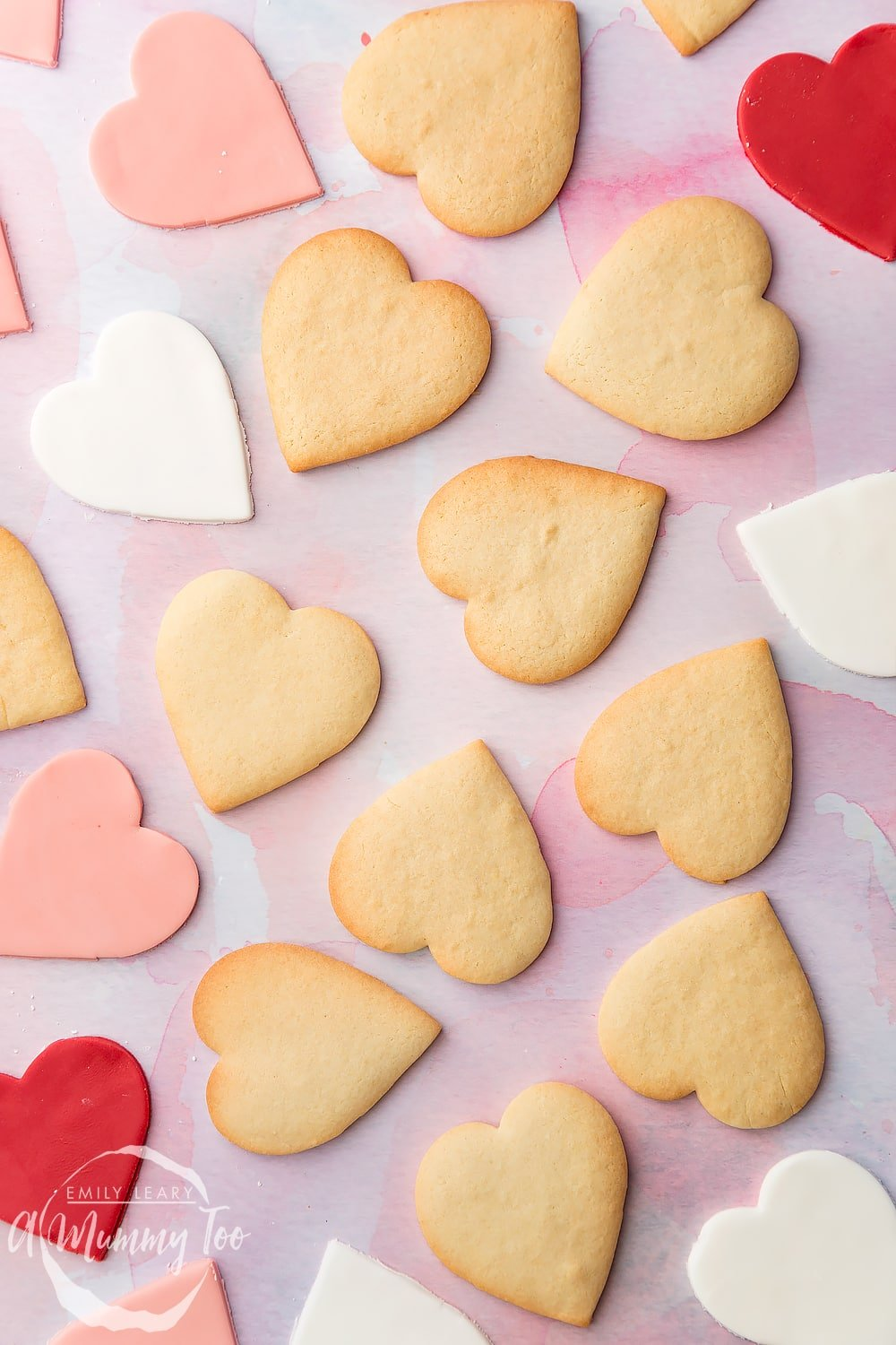 Overhead shot of heart shaped biscuits and fondant pieces with A Mummy Too logo in the bottom left hand corner
