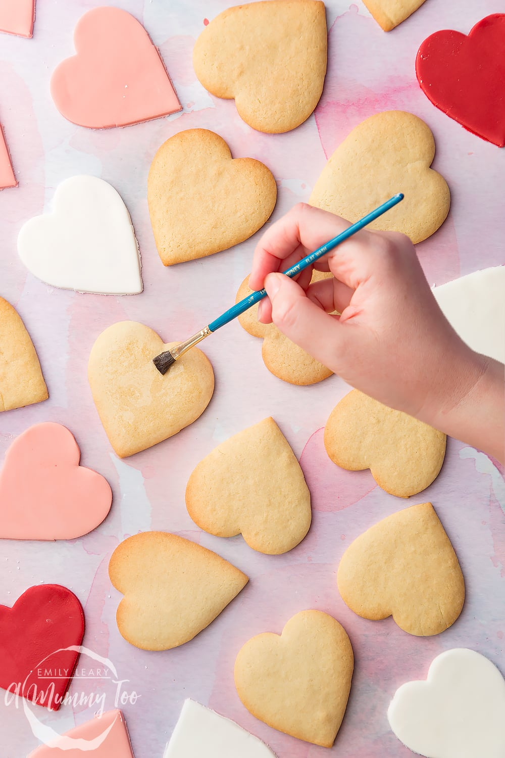 Overhead shot of a hand holding a brush and glazing heart shaped biscuits with icing sugar with the A Mummy Too logo in the bottom left hand corner