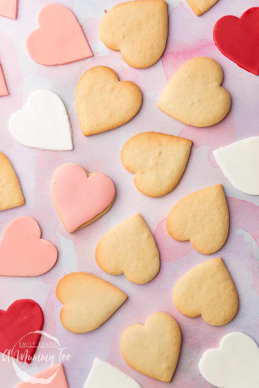 Overhead shot of heart shaped biscuits with some topped with pink fondant with the A Mummy Too logo in the bottom left hand corner